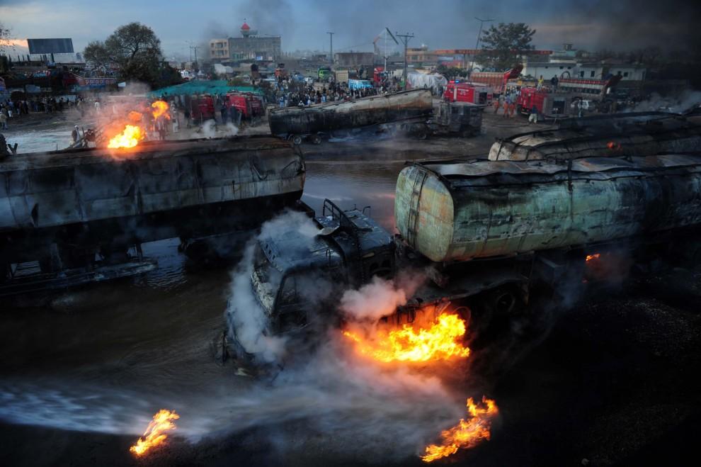 22. PAKISTAN, Peszawar, 26 lutego 2011: Dogaszanie zbiorników z paliwem uszkodzonych w wyniku zamachu bombowego. AFP PHOTO/ A. MAJEED