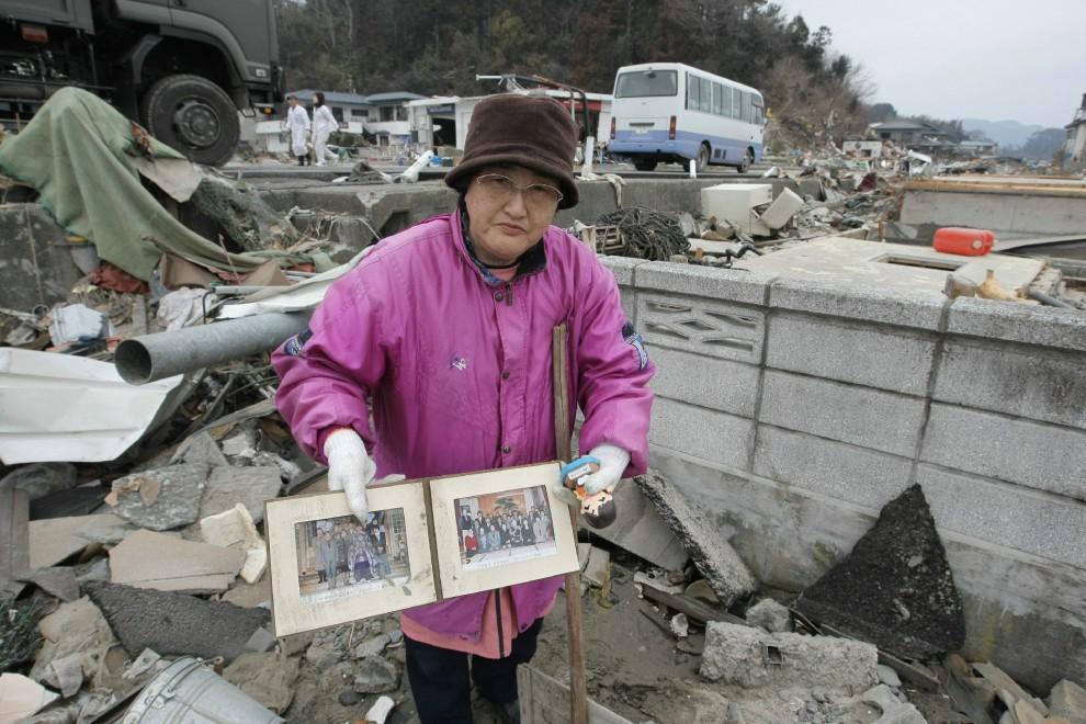 22. JAPONIA, Yamada, 15 marca 2011: Kobieta pokazuje rodzinne fotografie wydobyte ze zniszczonego domu. AFP PHOTO/JIJI PRESS