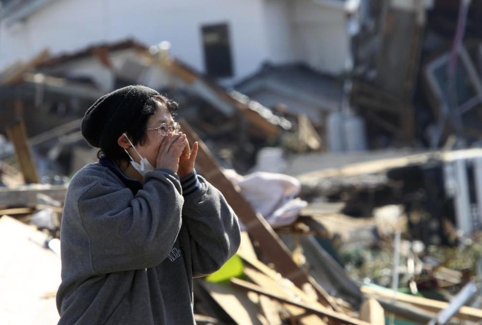 23. JAPONIA, Soma, 14 marca 2011: Kobieta nawołująca bliskich, którzy mogą być uwięzieni pod gruzami domu. AFP PHOTO / YOMIURI SHIMBUN