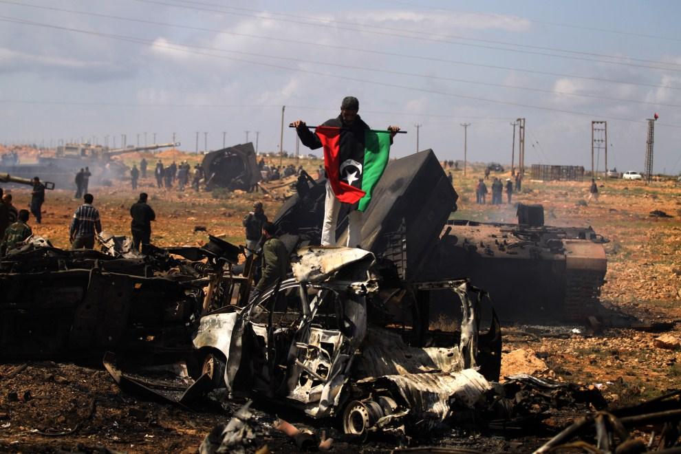 24. LIBIA, Al-Wayfiyah, 20 marca 2011: Rebeliant z dawną flagą w pobliżu zniszczonego konwoju lojalistów.AFP PHOTO/PATRICK BAZ
