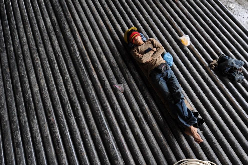 26. INDONEZJA, Dżakarta, 17 marca 2011: Mężczyzna zatrudniony przy budowie wieżowca odpoczywa podczas przerwy w pracy. AFP PHOTO / ROMEO GACAD