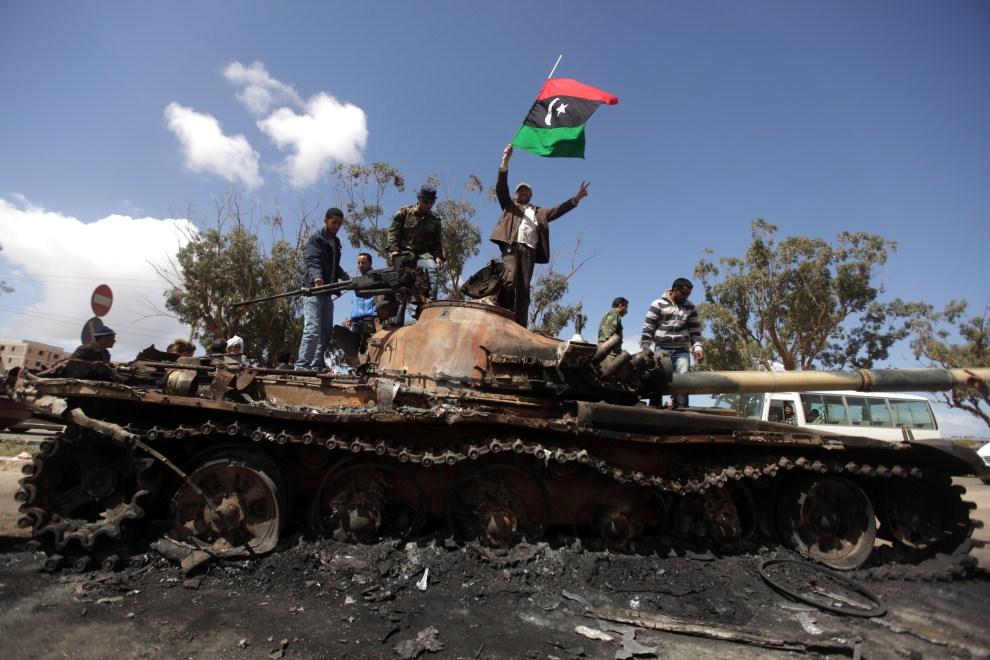 25. LIBIA, Al-Wayfiyah, 20 marca 2011: Rebelianci na zniszczonym czołgu lojalistów. AFP PHOTO/PATRICK BAZ