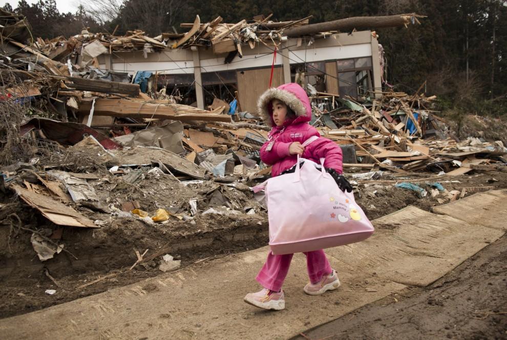 26. JAPONIA, Rikuzentakata, 15 marca 2011: Pięcioletnia Neena Sasaki niesie torbę z rzeczami, które udało jej się wydobyć ze zniszczonego domu. (Foto: Paula Bronstein /Getty Images)
