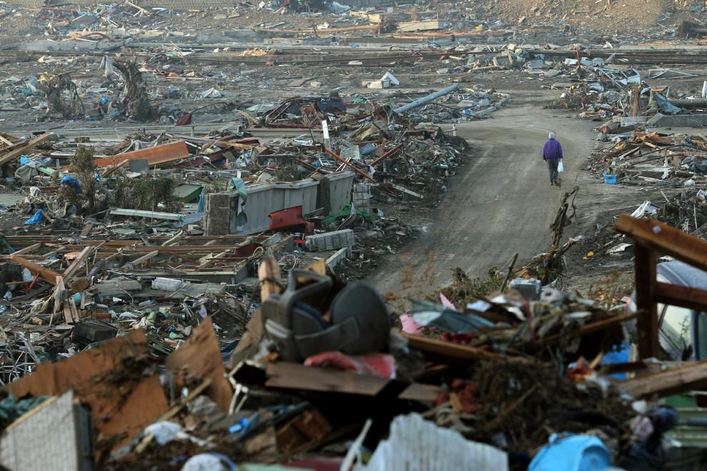 28. JAPONIA, Onagawa, 14 marca 2011: Mężczyzna przechodzi pomiędzy gruzami zniszczonych domów. AFP PHOTO / JIJI PRESS