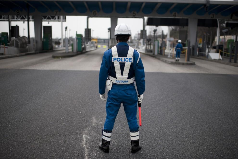 28. JAPONIA, Saitama, 15 marca 2011: Policjant kierujący ruchem na autostradzie przeznaczonej wyłącznie dla pojazdów ratunkowych. AFP PHOTO / FRED DUFOUR