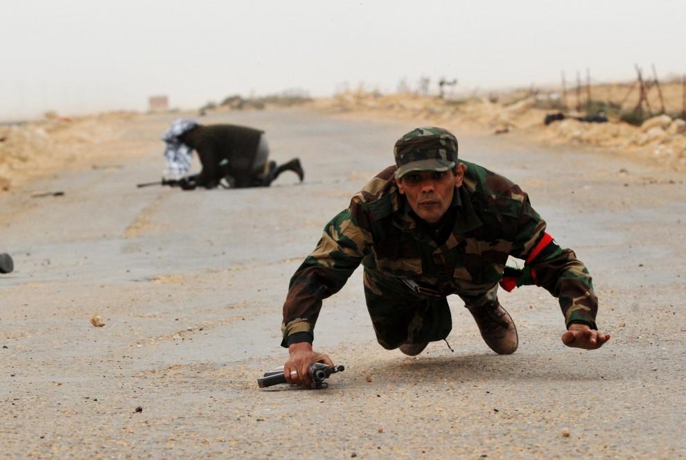 28. LIBIA, Bin Jawad, 8 marca 2011: Rebelianci kryją się przed pobliską eksplozją. AFP PHOTO / ROBERTO SCHMIDT