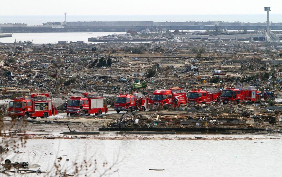 29. JAPONIA, Tokio, 13 marca 2011: Konwój samochodów ratowniczych przejeżdża wśród zniszczonych zabudowań. AFP PHOTO / JIJI PRESS
