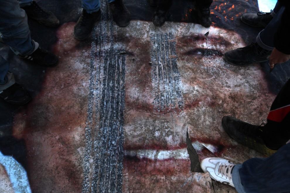 2. LIBIA, Bengazi, 28 lutego 2011: Plakat z wizerunkiem Muammara Kadafiego deptany przez protestujących. AFP PHOTO/PATRICK BAZ