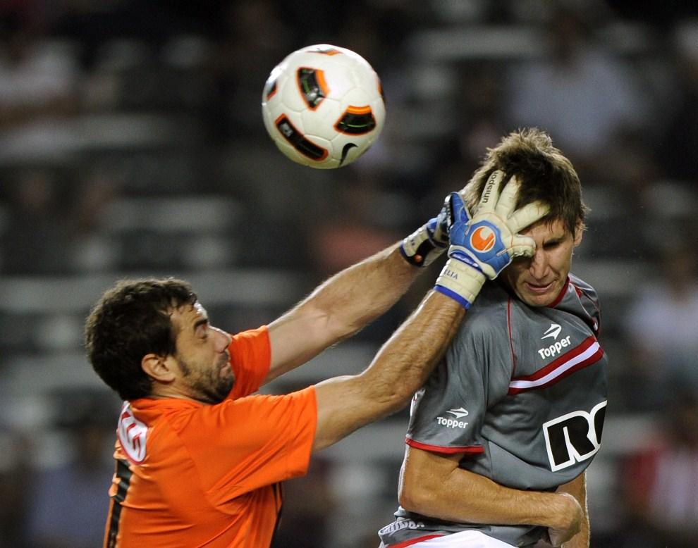31.ARGENTYNA, La Plata, 17 marca 2011:  Bramkarz Pablo Aurrecochea (po lewej) walczy o piłkę z obrońcą Estudiantes de La Plata – Federico Fernandezem (po prawej). AFP PHOTO / Juan Mabromata