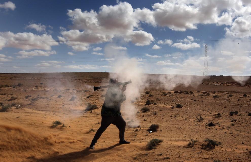 31. LIBIA, Bin Jawad, 6 marca 2011: Rebeliant ostrzeliwuje pozycje lojalistów. (Foto:  John Moore/Getty Images)