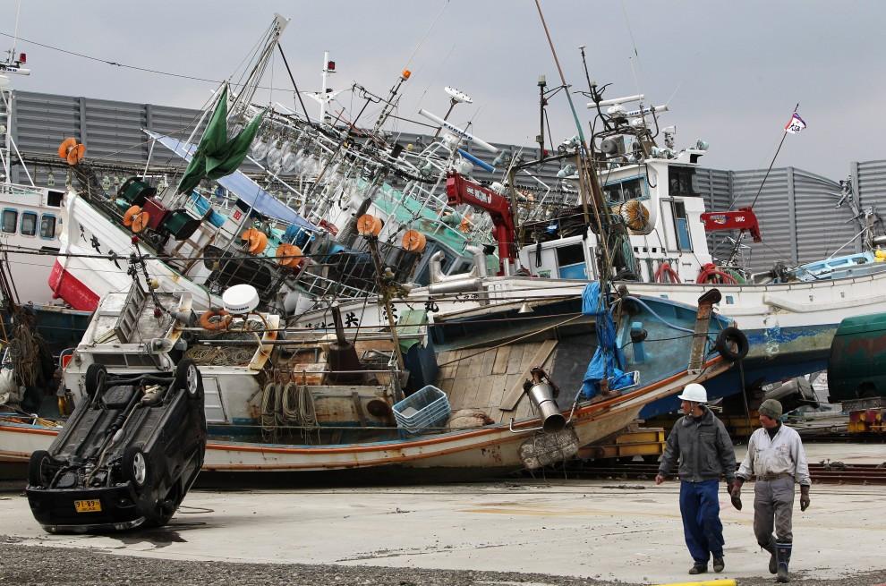 31. JAPONIA, Hachinohe, 14 marca 2011: Pracownicy portowi przechodzą obok uszkodzonych jednostek. EPA/HOW HWEE YOUNG