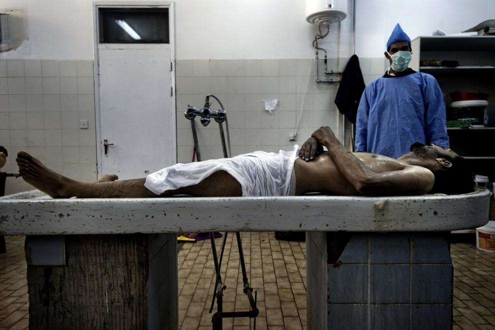 33. LIBIA, Benghazi, 7 marca 2011: Ciało poległego rebelianta złożone w kostnicy. AFP PHOTO/GIANLUIGI GUERCIA