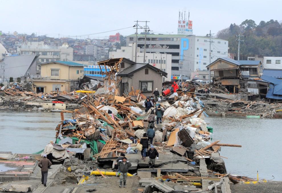 34. JAPONIA, Ishinomaki, 15 marca 2011: Mieszkańcy Ishinomaki przechodzą przez uszkodzony most. AFP PHOTO / KIM JAE-HWAN