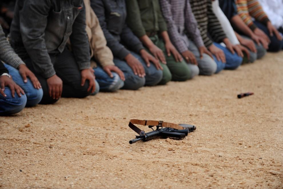 34. LIBIA, Ras Lanuf, 4 marca 2011: Rebelianci podczas modlitwy przed zbliżającą się bitwą. AFP PHOTO / ROBERTO SCHMIDT