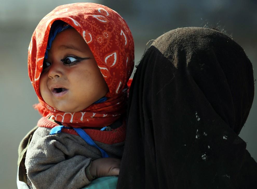 37. AFGANISTAN, Garmser, 7 marca 2011: Afganka niesie na rękach swoją młodszą siostrę. AFP PHOTO / ADEK BERRY