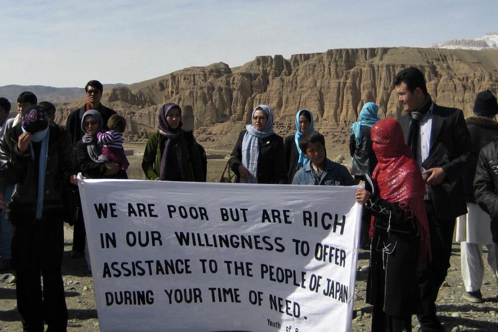 """38. AFGANISTAN, Bamiyan, 14 marca 2011: Afgańczycy trzymający transparent z napisem: """"Nie mamy wiele, ale jesteśmy bogaci w chęć pomocy narodowi Japonii, który znalazł się w potrzebie."""" AFP PHOTO/HO/UNAMA/Mohamad Ali Danish"""