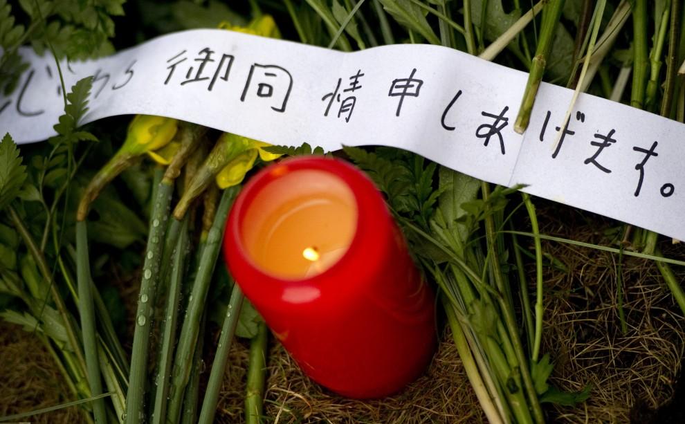 40. NIEMCY, Berlin, 14 marca 2011: Zapalona świeca i kwiaty złożone przed ambasadą Japonii. AFP PHOTO / JOHANNES EISELE