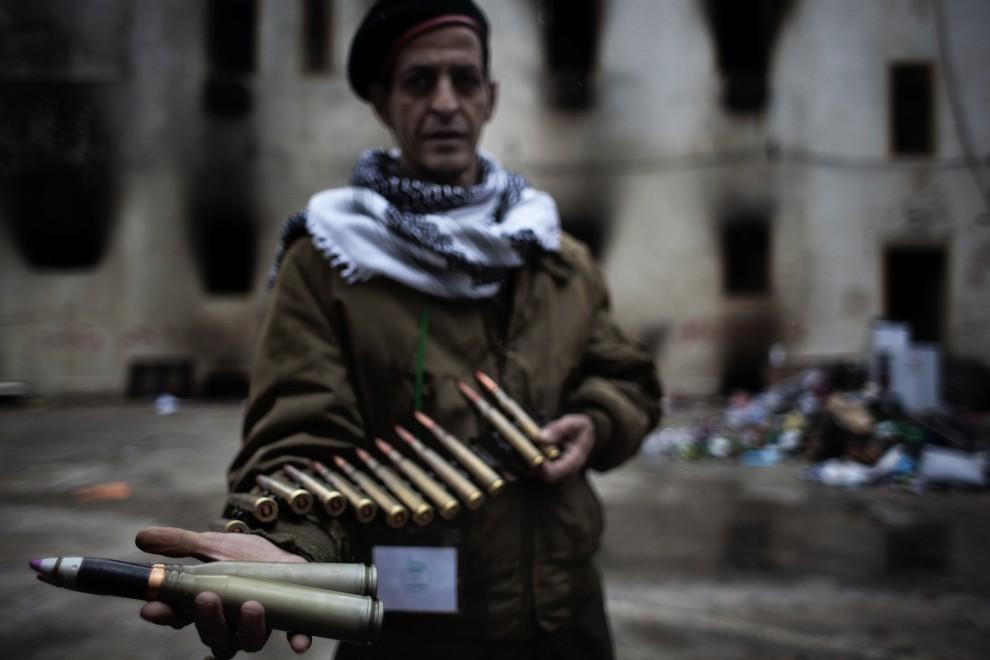 4. LIBIA, Bengazi, 27 lutego 2011: Żołnierz pokazuje amunicję, która miała zostać użyta przeciw protestującym. AFP PHOTO/MARCO LONGARI
