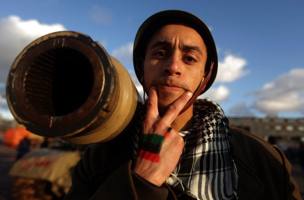 4. LIBIA, Benghazi, 27 lutego 2011: Mężczyzna pozuje do zdjęcia obok zniszczonego czołgu. AFP PHOTO/PATRICK BAZ