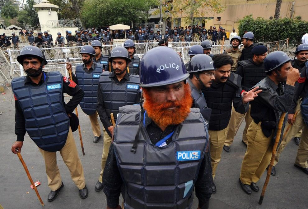 5. PAKISTAN, Lahore, 17 marca 2011: Oddział policji ochrania konsulat USA przed protestującymi studentami. Protesty wybuchły po uwolnieniu Raymonda Davisa – agenta CIA, oskarżonego o zabójstwo. AFP PHOTO/ARIF ALI