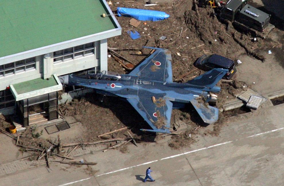 5. JAPONIA, Higashimatsushima, 14 marca 2011: Samolot wepchnięty przez wodę do hangaru. AFP PHOTO / NOBORU HASHIMOTO