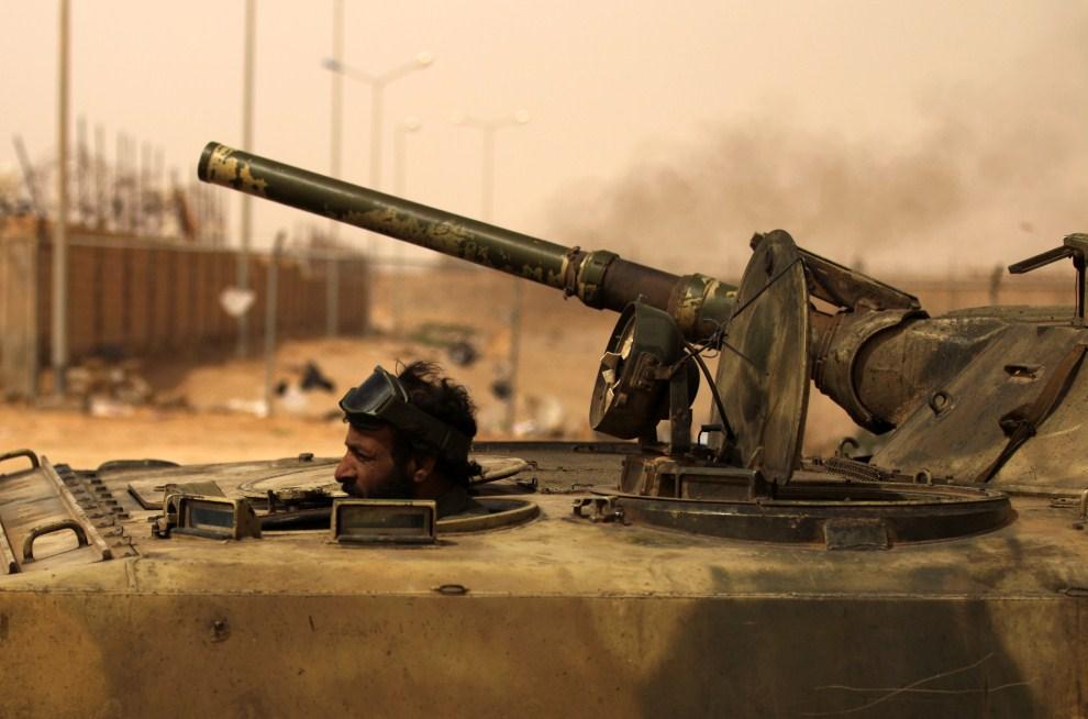 6. LIBIA, Adżdabija, 14 marca 2011: Libijski powstaniec prowadzi czołg na miejsce walk z oddziałami  Muammara Kadafiego. AFP PHOTO/PATRICK BAZ