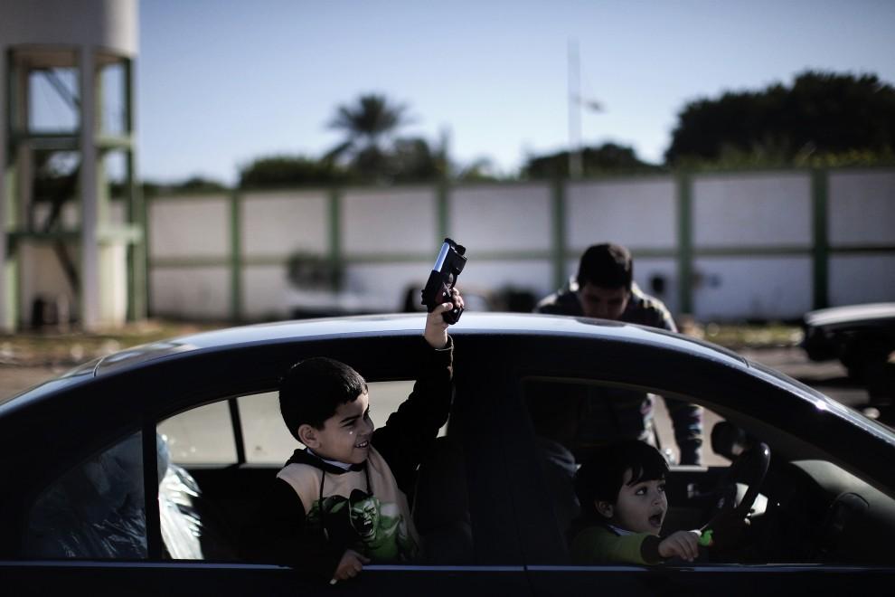 8. LIBIA, Bengazi, 27 lutego 2011: Libijski chłopiec z pistoletem-zabawką. AFP PHOTO / MARCO LONGARI