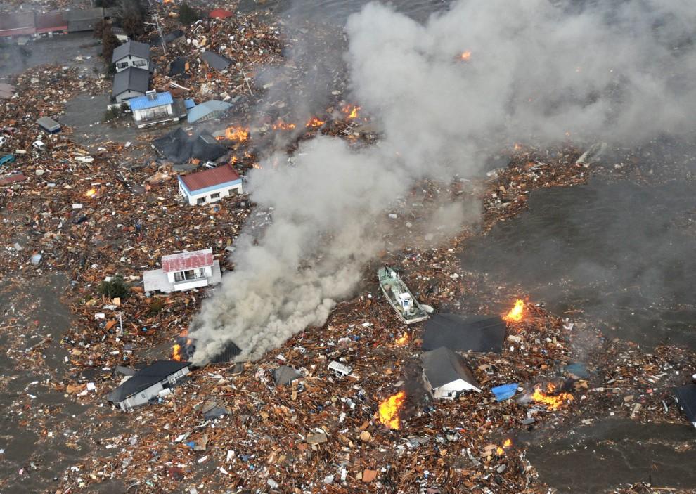 8. JAPONIA, Sendai, 15 marca 2011: Domy i płonące szczątki niesione przez falę. EPA/AFLO/Mainichi Newspaper