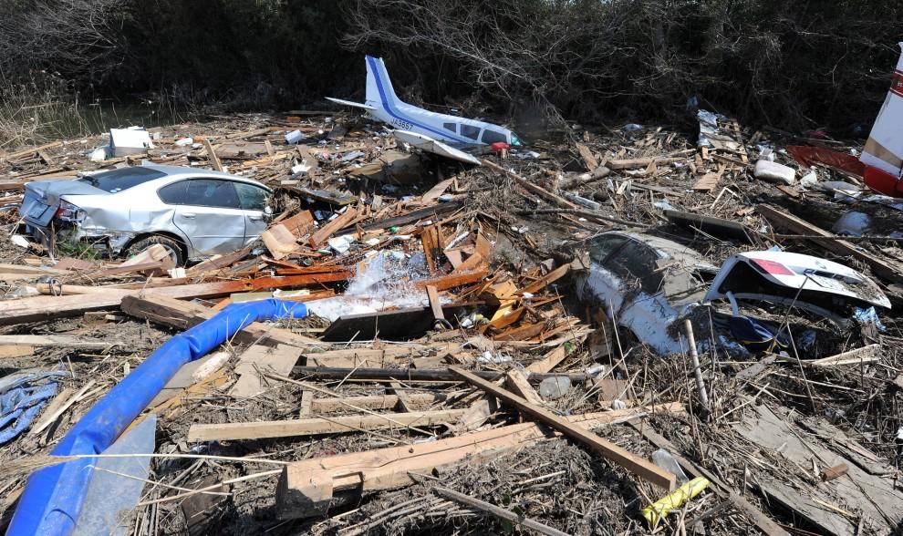 9. JAPONIA, Natori, 13 marca 2011: Samolot i samochody, które niosła fala tsunami. AFP PHOTO / MIKE CLARKE
