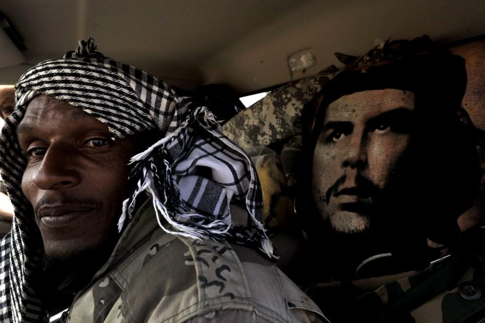 """10. LIBIA, Bin Jawad, 27 marca 2011: Rebeliant we wnętrzu samochodu obok podobizny  Ernesto """"Che"""" Guevary. AFP PHOTO / ARIS MESSINIS"""