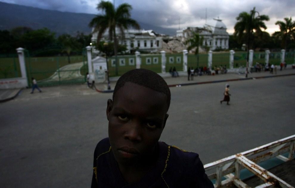 10. HAITI, Port-au-Prince, 6 kwietnia 2011: Chłopiec na tle zniszczonego w 2010 pałacu prezydenckiego. AFP PHOTO / Hector Retamal