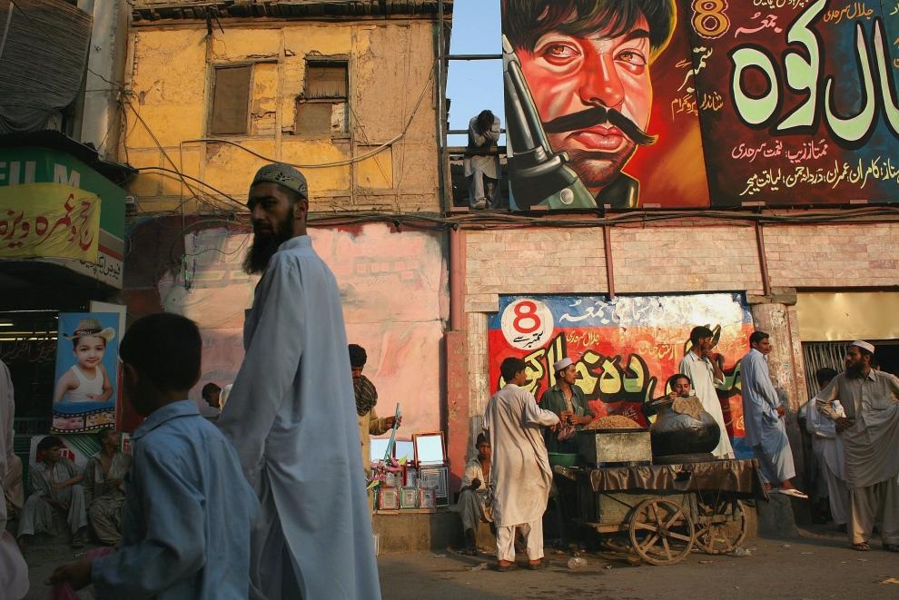 10. PAKISTAN, Peszawar, 8 września 2009: Ojciec z synem (na pierwszym planie) mijają mural reklamujący wyświetlany w kinie film. (Foto: John Moore/Getty Images)