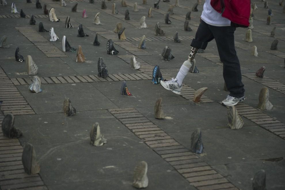 12. KOLUMBIA, Bogotá, 4 kwietnia 2011: Mężczyzna, który stracił nogę w wyniku eksplozji miny, przechodzi obok 9133 butów upamiętniających pozostał ofiary min z lat 1990 –   2010. AFP PHOTO/EITAN ABRAMOVICH