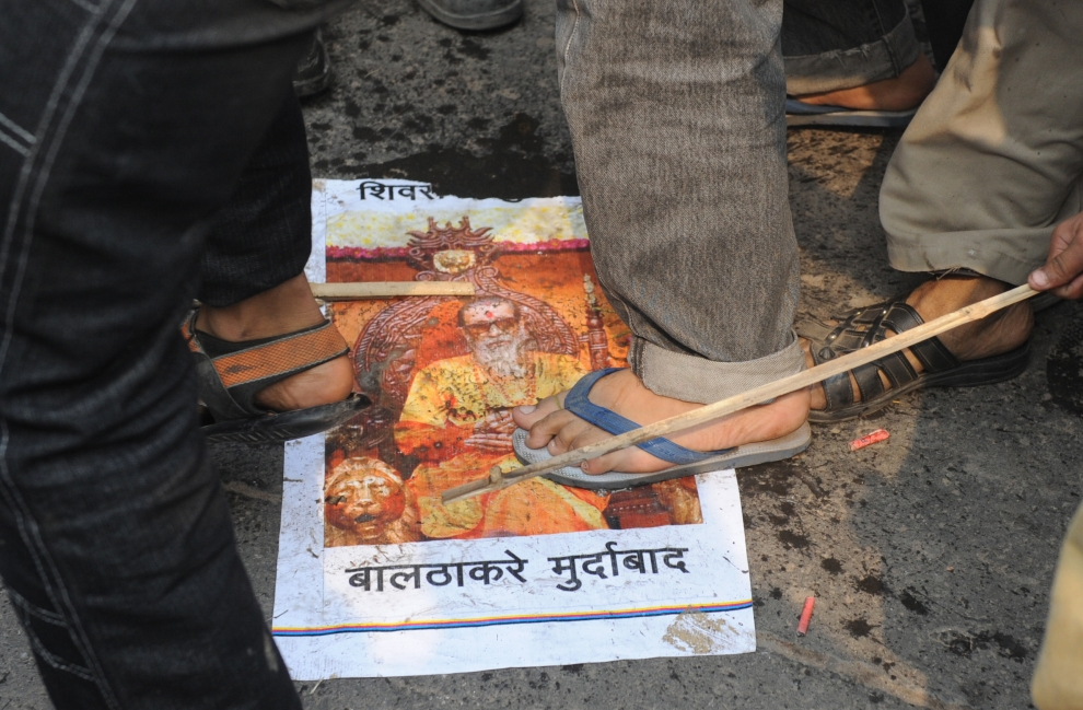 """13. INDIE, New Delhi, 12 lutego 2010: Widzowie przed kinem, gdzie wyświetlany jest film """"My Name is Khan"""". Pod ich stopami ulotka nacjonalistycznej partii Shiv Sena. AFP   PHOTO/Prakash SINGH"""