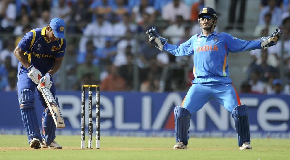 15. INDIE, Bombaj, 2 kwietnia 2011: Kapitan reprezentacji Indii – Mahendra Singh Dhoni (po prawej) cieszy się z wyautowania  zawodnika drużyny przeciwnej. AFP   PHOTO/Indranil MUKHERJEE