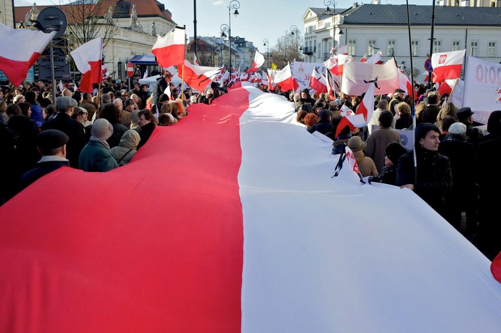 15. POLSKA, Warszawa, 10 kwietnia 2011: Ludzie niosący olbrzymią flagę przed Pałacem Prezydenckim. AFP PHOTO / Marcin Lobaczewski