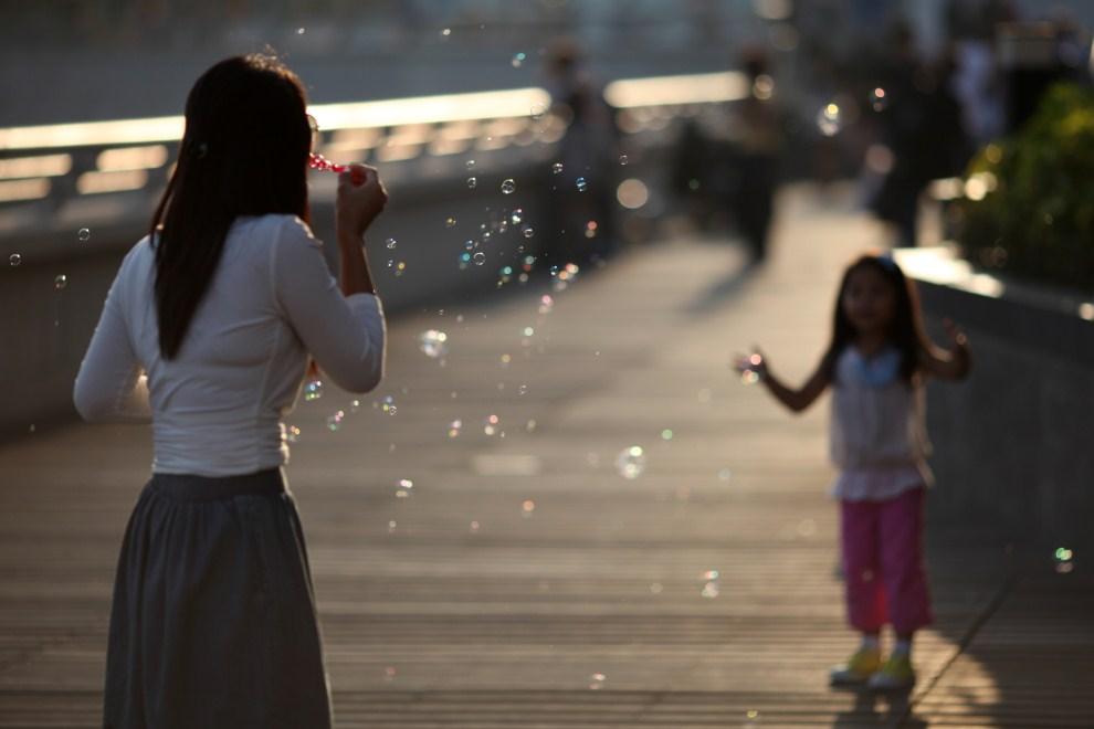 16. CHINY, Hongkonkg, 9 kwietnia 2011: Kobieta puszcza bańki mydlane w kierunku dziecka. AFP PHOTO / ED JONES