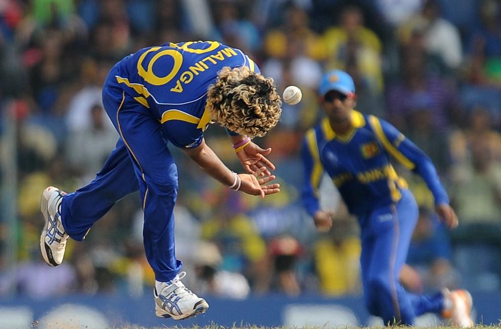 17. SRI LANKA, Colombo, 29 marca 2011: Lasith Malinga (Sri Lanka) stara się złapać piłkę podczas spotkania półfinałowego Mistrzostw Świata w Krykiecie. AFP PHOTO / Lakruwan WANNIARACHCHI