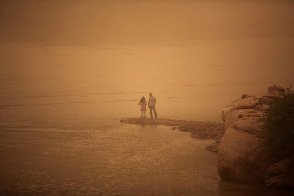 17. IRAN, Ahvaz, 13 kwietnia 2011: Para nad brzegiem Arvandrud w trakcie burzy piaskowej. AFP PHOTO/MOHAMMAD REZA DEHDARI