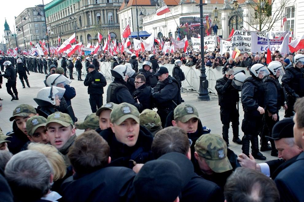 18. POLSKA, Warszawa, 10 kwietnia 2011: Policja stara się nie dopuścić do przerwania kordonu wokół Pałacu Prezydenckiego. AFP PHOTO / Marcin Lobaczewski