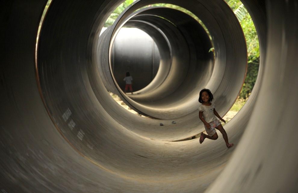 19. FILIPINY, Manila, 4 kwietnia 2011: Dzieci bawią się w stalowych rurach, które posłużą do budowy wodociągu. AFP PHOTO