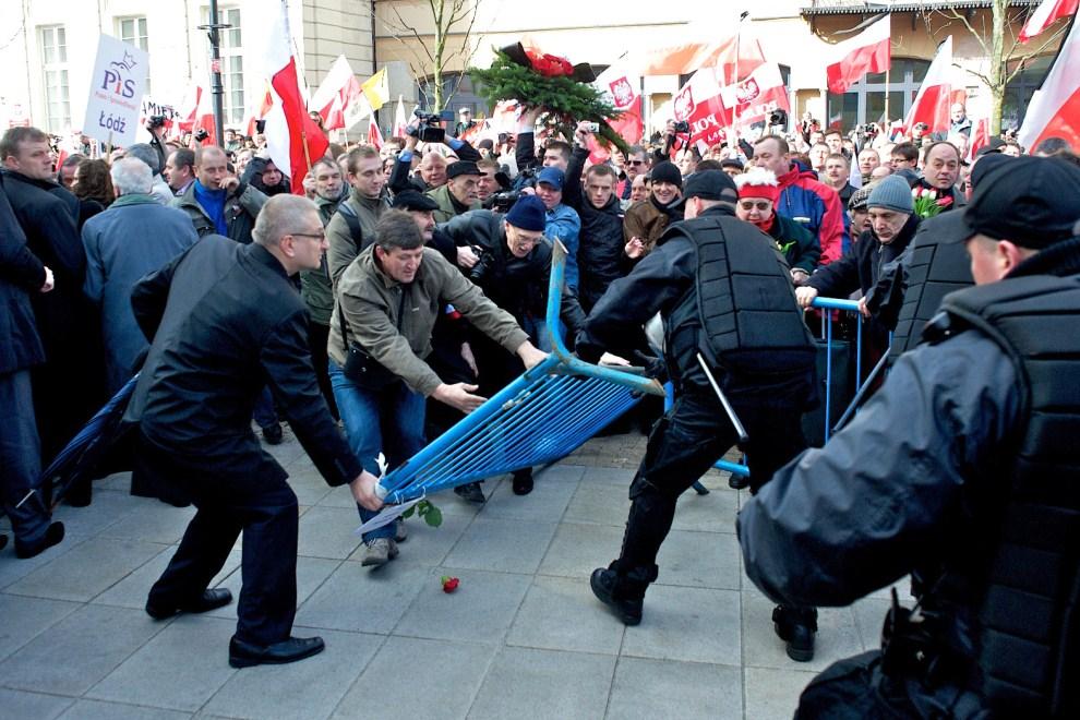 20. POLSKA, Warszawa, 10 kwietnia 2011: Ludzie zebrani przed Pałacem Prezydenckim przerywają linię barier rozstawionych przez policję. AFP PHOTO / Marcin Lobaczewski