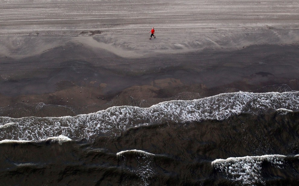 21. USA, Grand Isle, 13 kwietnia 2011: Kobieta spacerująca plażą na Grand Isle. Mario Tama/Getty Images/AFP