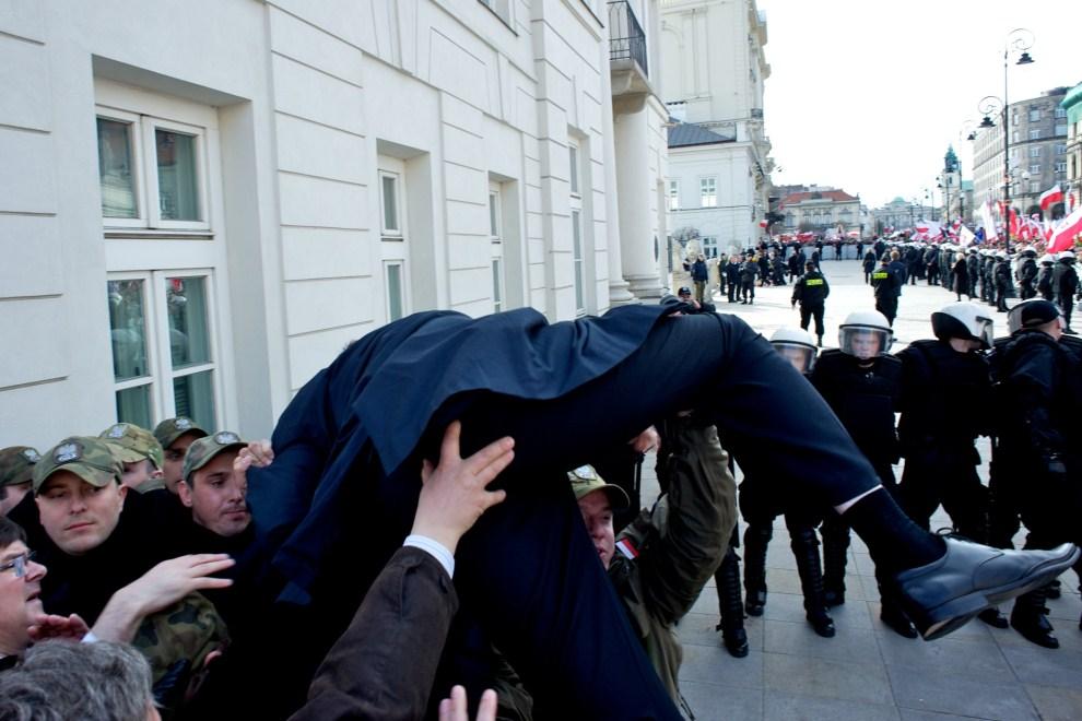 21. POLSKA, Warszawa, 10 kwietnia 2011: Członek PiS usiłujący przejść ponad barierką policyjną. AFP PHOTO / Marcin Lobaczewski