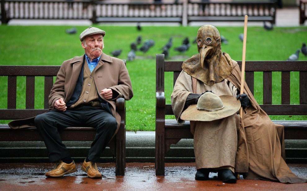 22. WIELKA BRYTANIA, Glasgow, 31 marca 2011: Artysta cyrkowy (po prawej) w kostiumie średniowiecznego lekarza walczącego z zarazą. (Foto: Jeff J Mitchell/Getty Images)