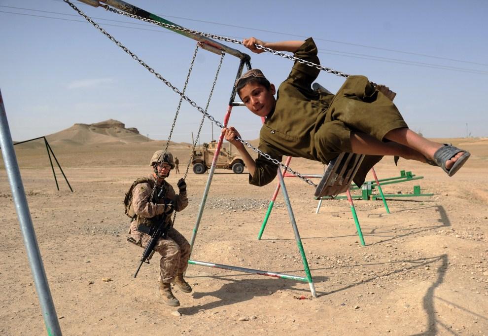 23. AFGANISTAN, Musa Qala, 12 kwietnia 2011: Kapitan Elizabeth Jackson (po lewej) na huśtawce z afgańskim chłopcem. AFP PHOTO/Peter PARKS