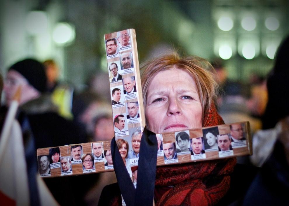 23. POLSKA, Warszawa, 10 kwietnia 2011: Kobieta trzyma krzyż z fotografiami ofiar katastrofy Tu-154M. AFP PHOTO / WOJTEK RADWANSKI