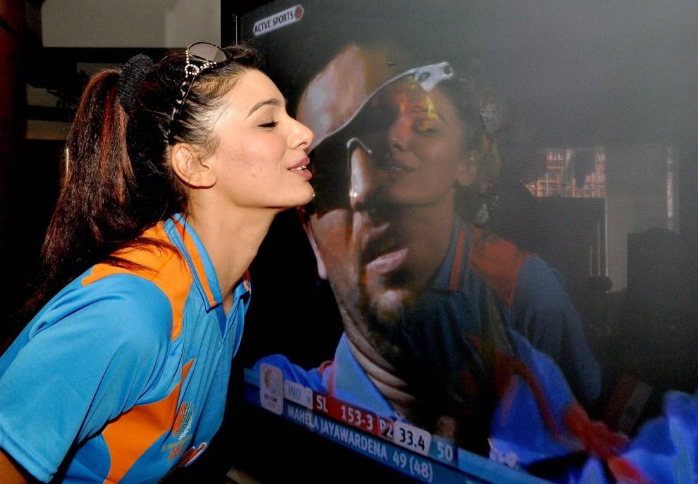 24. INDIE, Bombaj, 2 kwietnia 2011: Aktorka Mink Brar całuje ekran, gdzie widoczny jest zawodnik reprezentacji narodowej – Yuvraj Singh. AFP PHOTO/STR