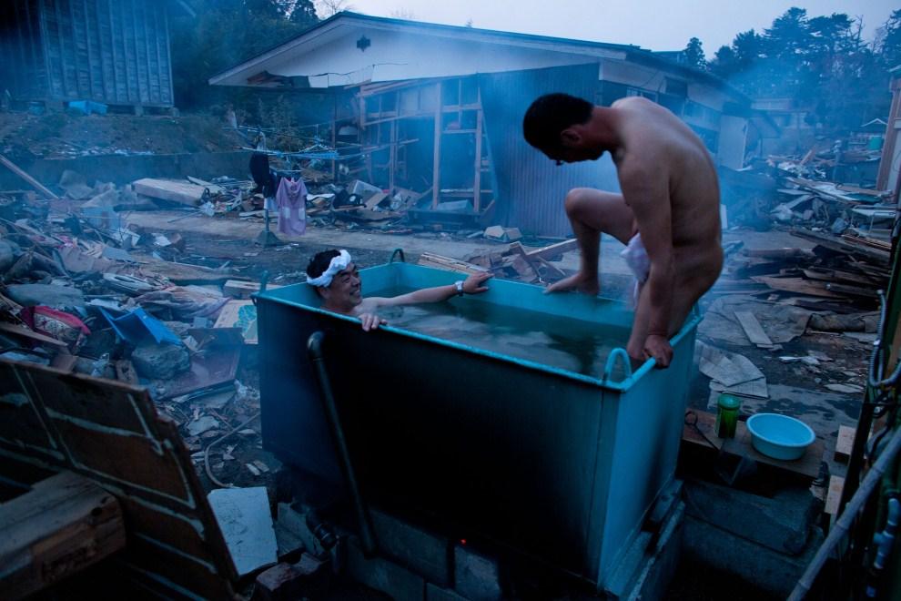 32. JAPONIA, Kesennuma, 14 kwietnia 2011: Mężczyźni biorą kąpiel pośród zniszczeń wywołanych przez trzęsienie ziemi i tsunami. AFP PHOTO / YASUYOSHI CHIBA