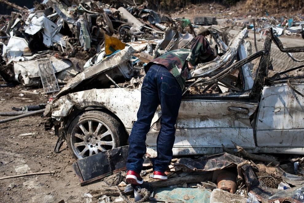 33. JAPONIA, Minamisanriku, 13 kwetnia 2011: Mężczyzna, który odnalazł swój samochód po miesiącu od przejścia fali tsunami. AFP PHOTO / YASUYOSHI CHIBA